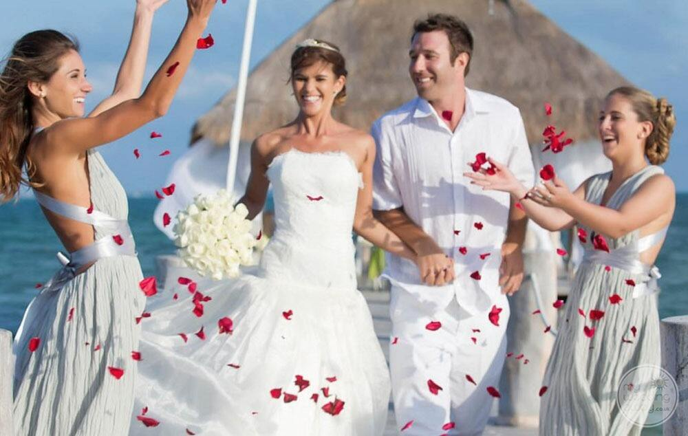 Wedding couple on the beach with ceremony gazebo in the background and bridesmaids throwing flower petals in air