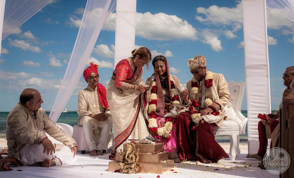 South Asian wedding couple having ceremony on the beach with the ocean in the background