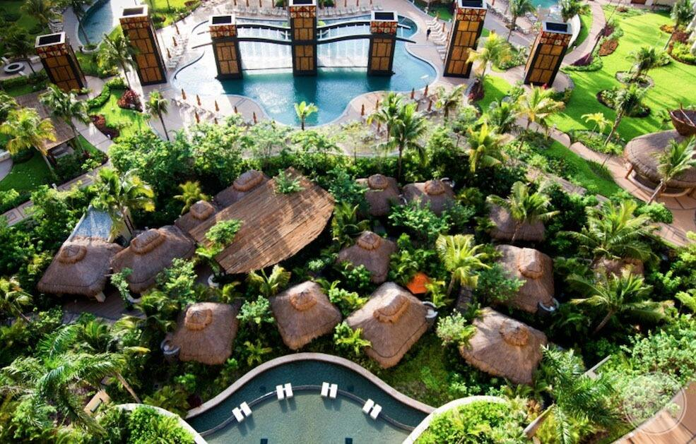 Aerial view of large cabana with main swimming pool and green grass and palm trees