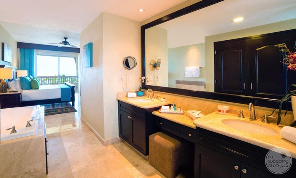 King bedroom bathroom with double vanity sinks and large soaker tub