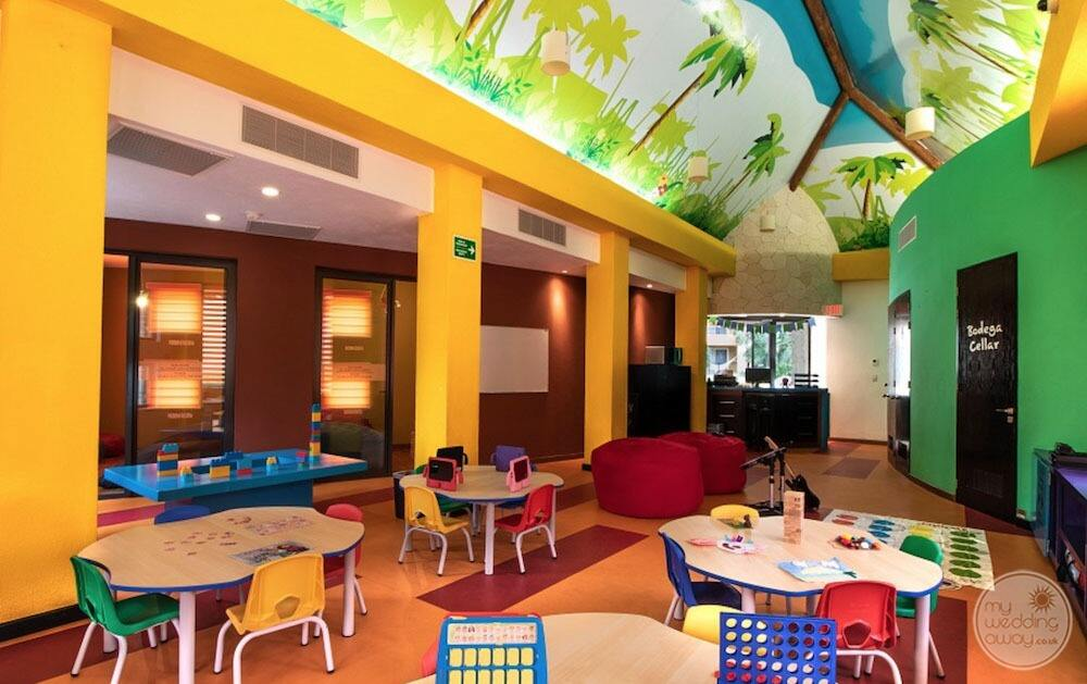 Colourful yellow and green walls children's play area with Green yellow and red chairs