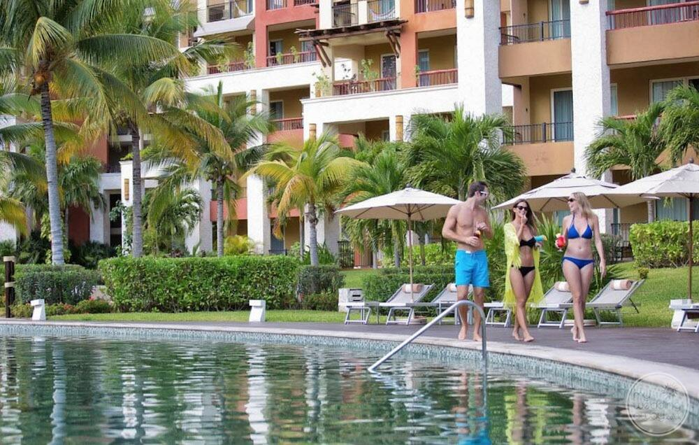 Resort guests walking by the pool with palm trees hedging and room buildings in the background
