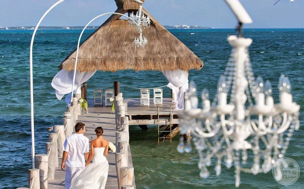 Wedding couple walking up the pier towards the gazebo with the wedding chairs and the ocean in the background