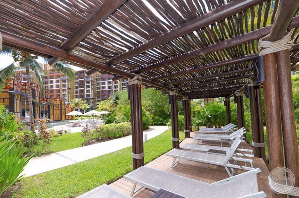Lounge chair is beside the pool and walkway with woof covering
