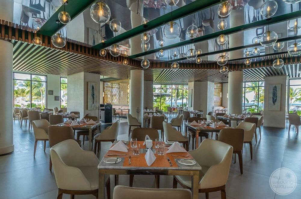 Restaurant dining area with beige leather chairs and bubble Glass ceiling lights