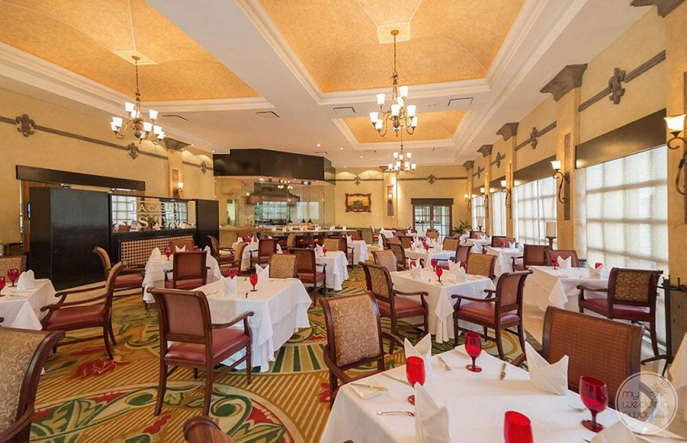 Main restaurant with yellow ceiling chandeliers red wine glasses and colourful carpet