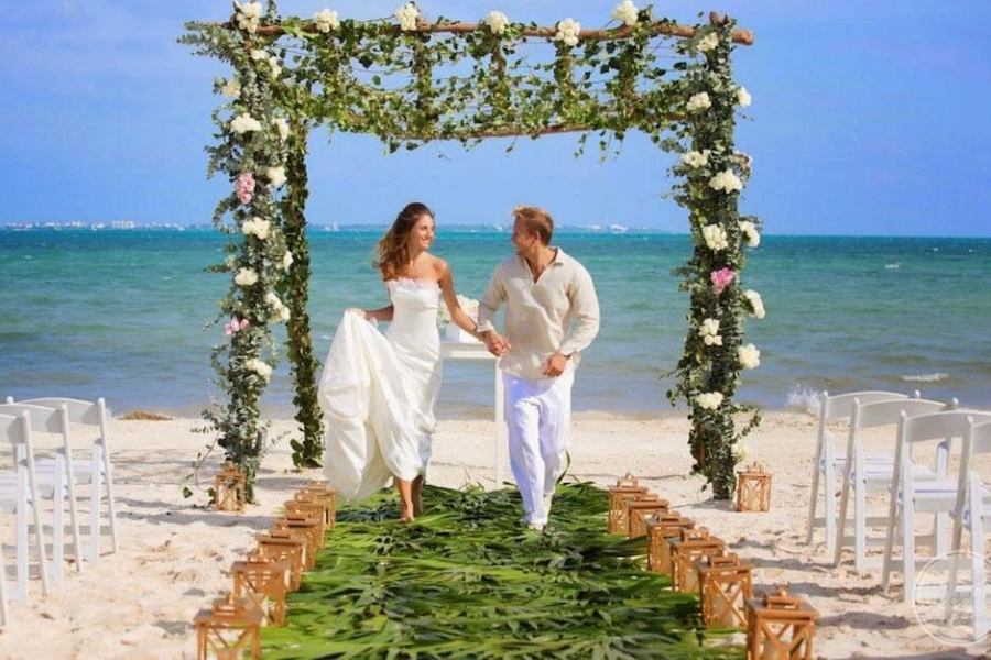 Wedding couple on the beach with ceremony flowers and gazebo above them and green palm runner along the white sand