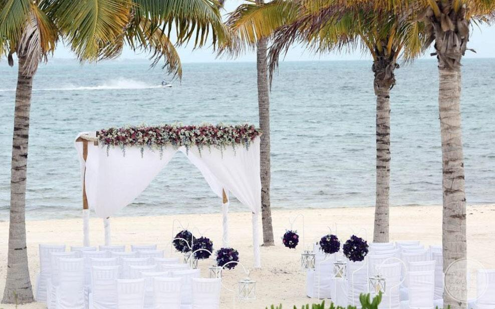 White gazebo on the beach with flowers and white wedding chairs and the ocean in the background
