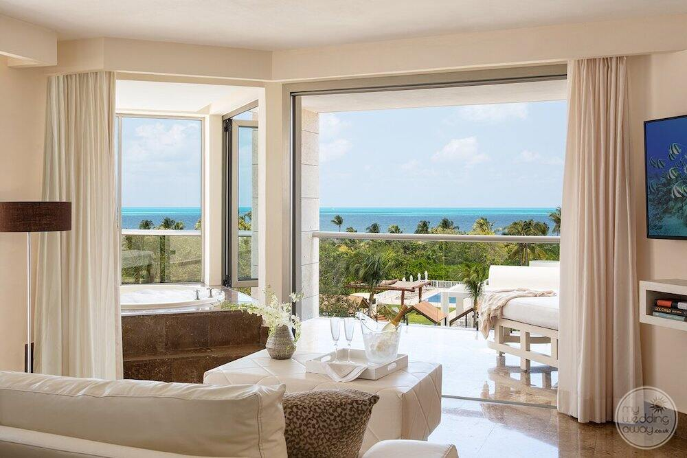 View of the living room and outdoor Jacuzzi and sitting furniture along with oceanview in the bedroom