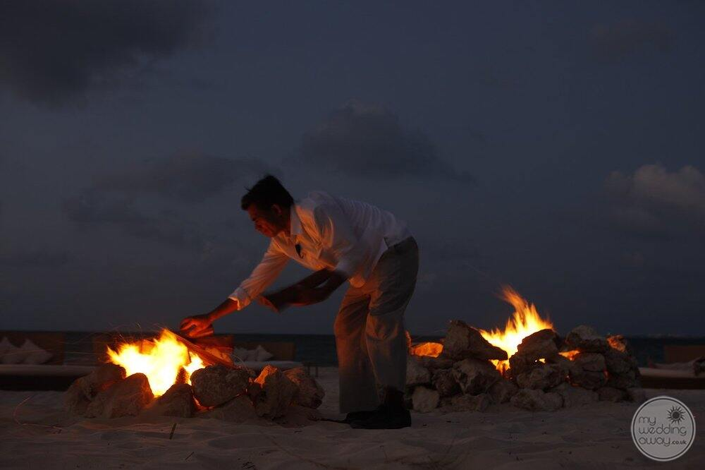 Evening fire on the beach with staff setting up Display