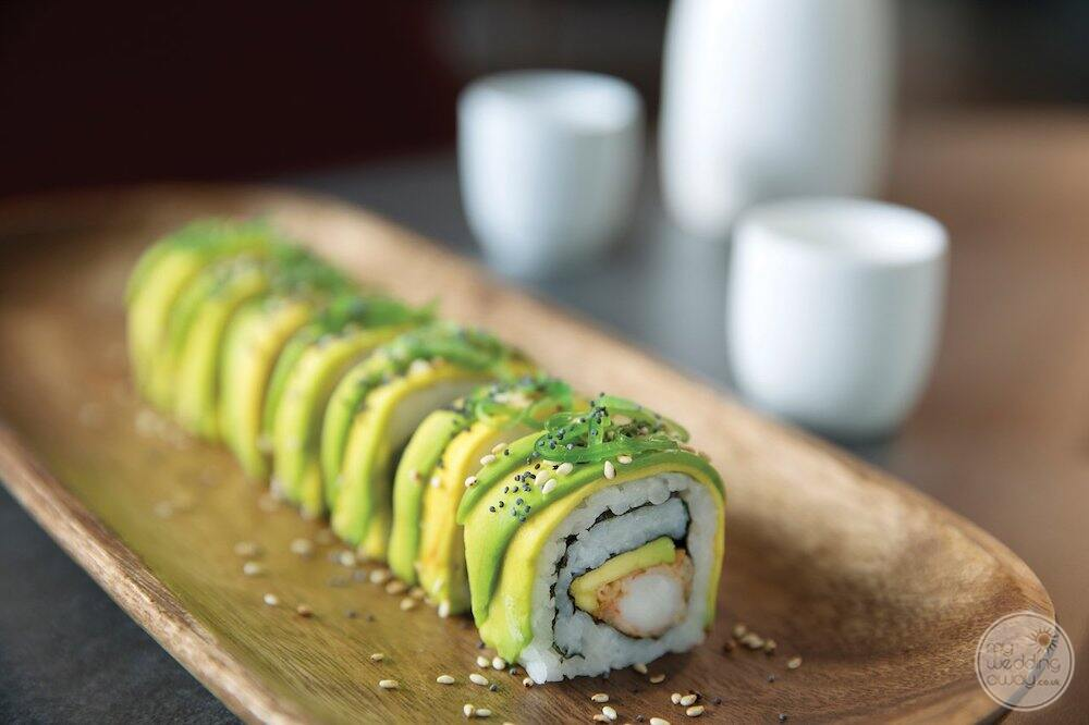 Sushi roll with avocado and seafood served on a wooden platter