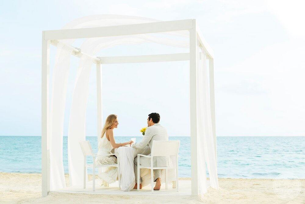 Couples on the beach and romantic gazebo enjoying dinner by the ocean