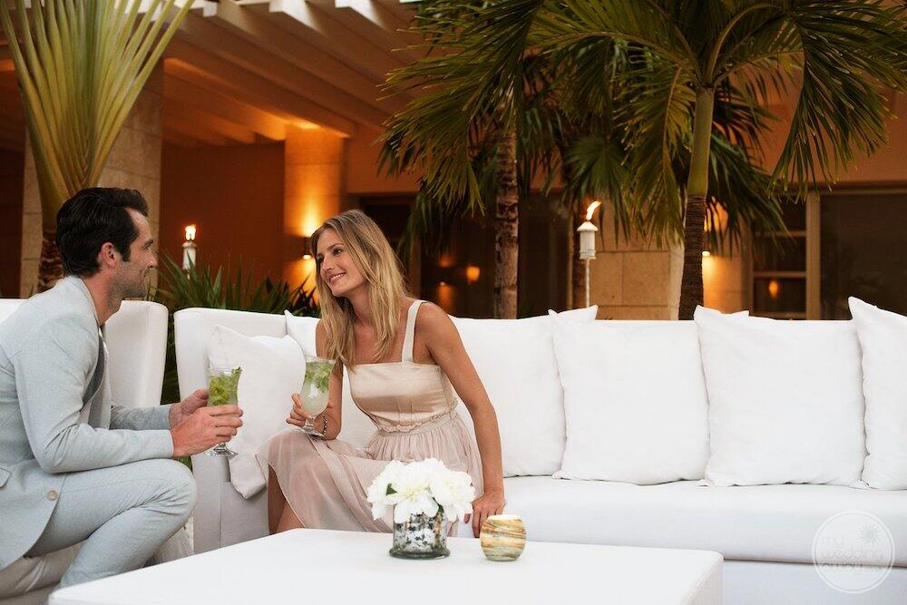 Couple drinking cocktails on a white couch with palm trees and the lighting in the background