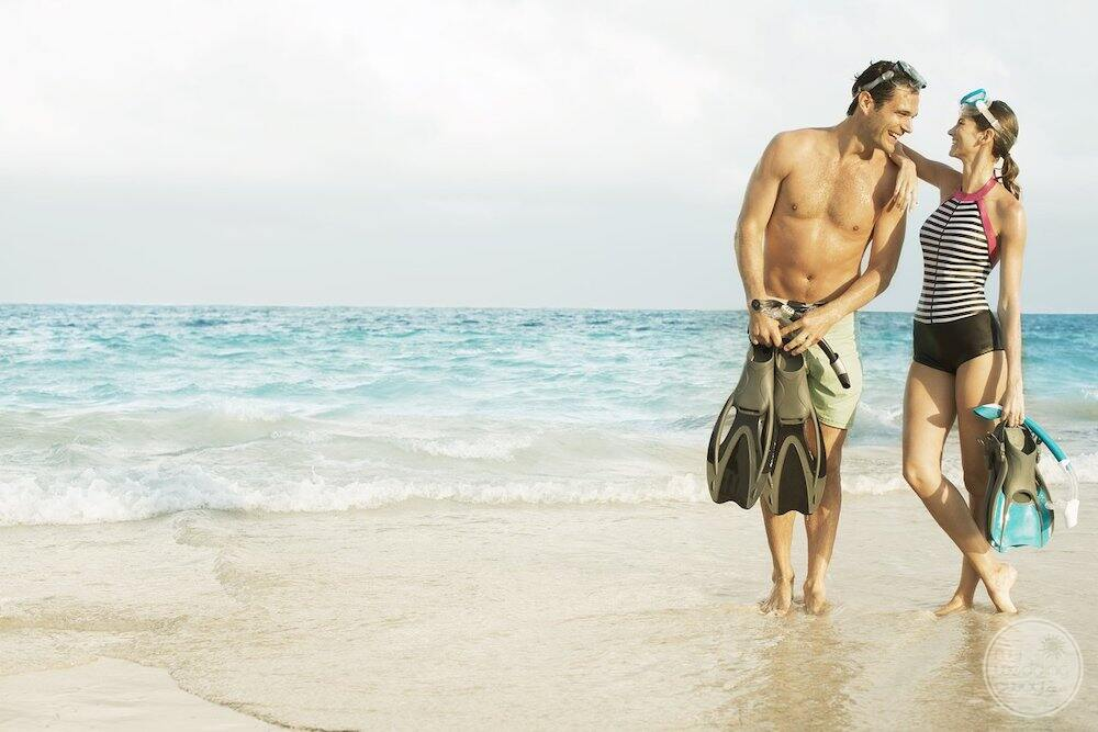 Couple holding snorkelling equipment on the beach beside the Caribbean ocean