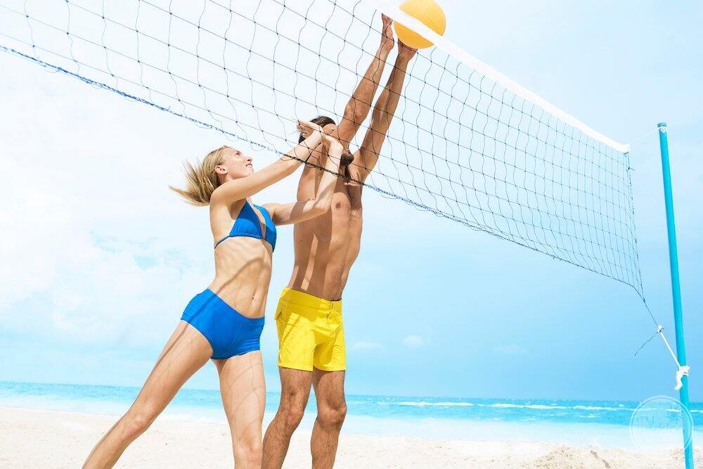 A man and a woman playing beach volleyball on the white sand beside the ocean