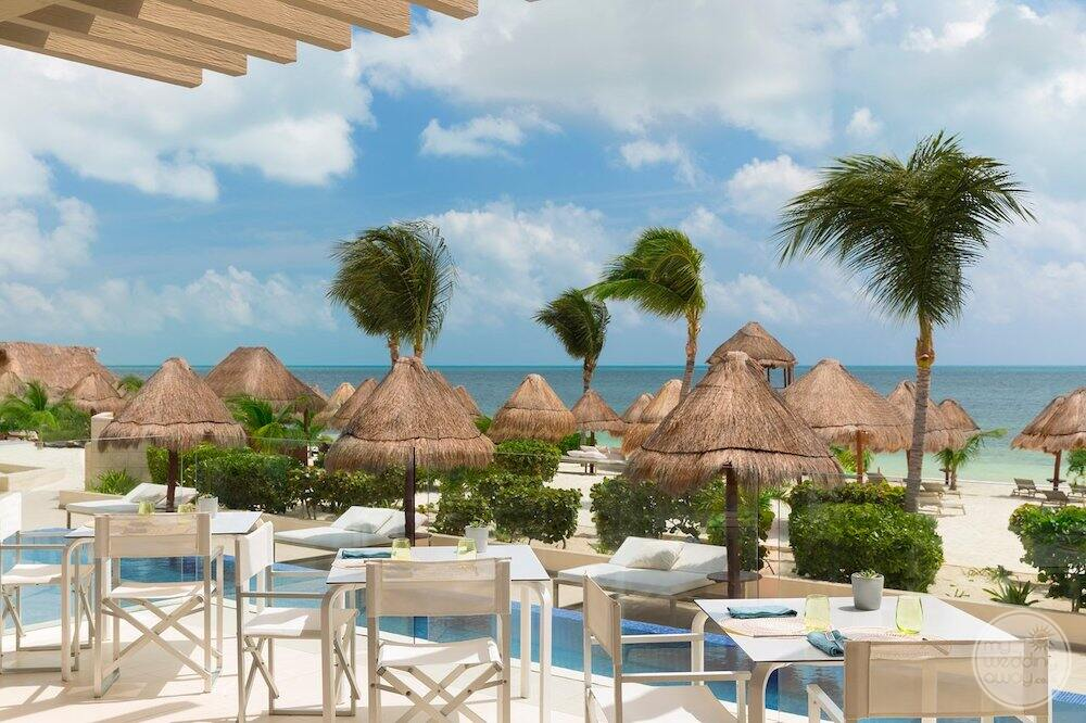 Outdoor dining area beside a pool thatched roof cabana and the beach