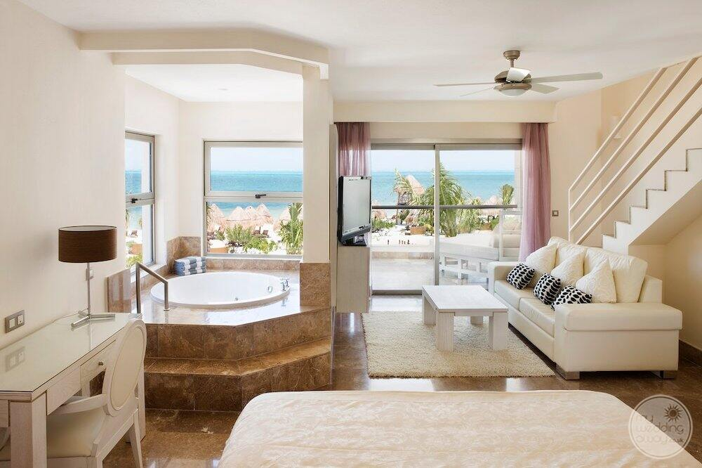 Main floor living room with white couch table desk bed and Jacuzzi tub