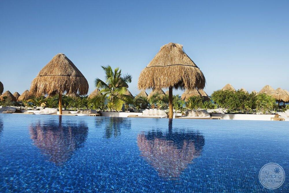 Main swimming infinity pool with thatched roof cabanas Palm trees and blue sky in the background
