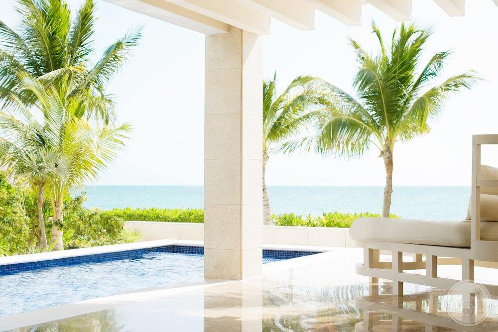 Outdoor room swim up suit with lounge chair palm trees ocean and plunge pool