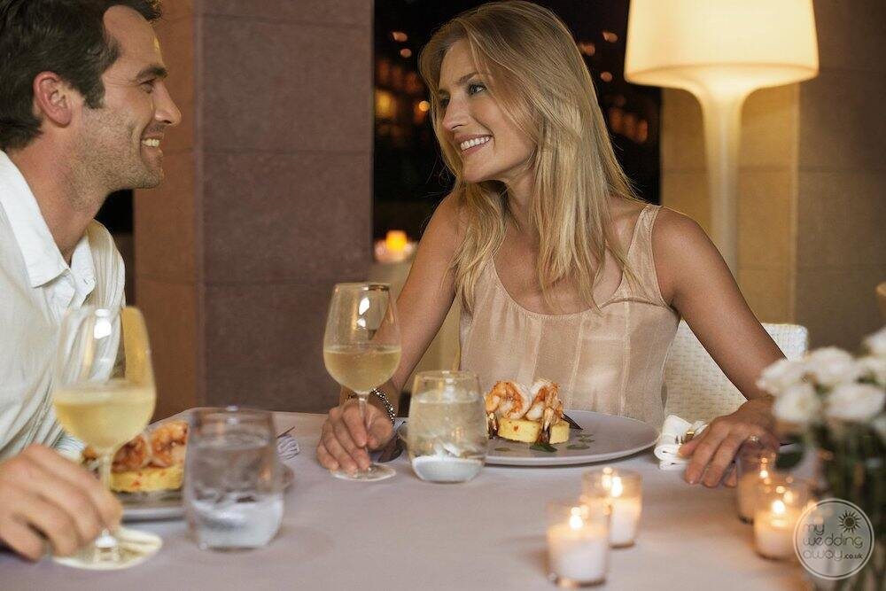 Couple enjoying evening meal with a white wine in the restaurant