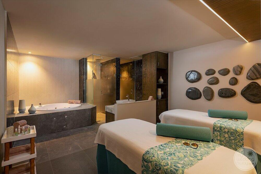Couples massage bed is located in the spa area with  deep soaker tab