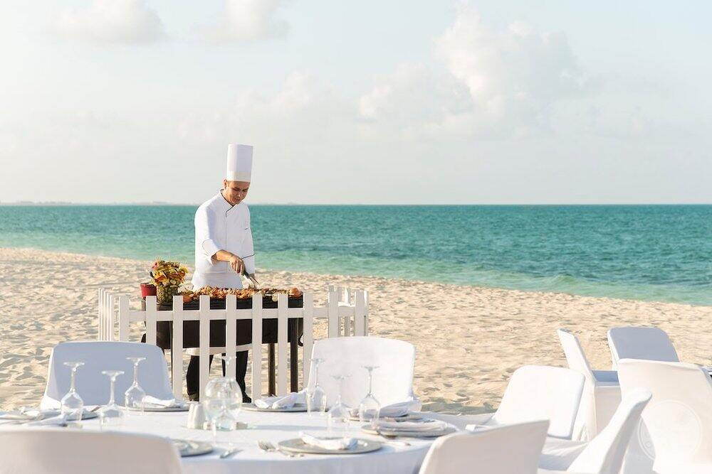 Chef preparing a meal on the beach with white linen tables and white chairs