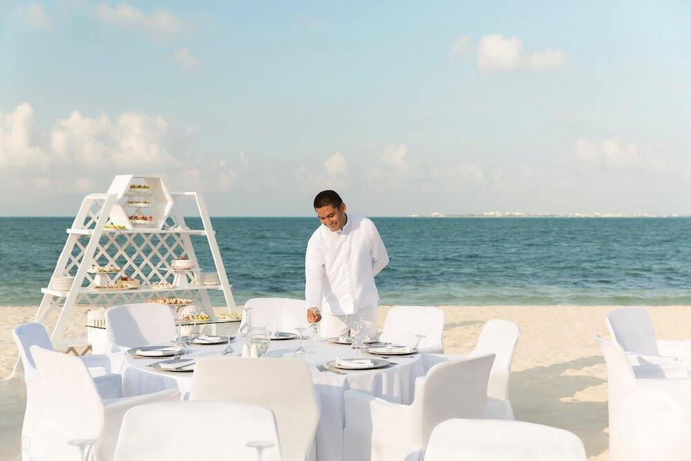 Dinner on the beach with chef setting up tables and buffet in the background