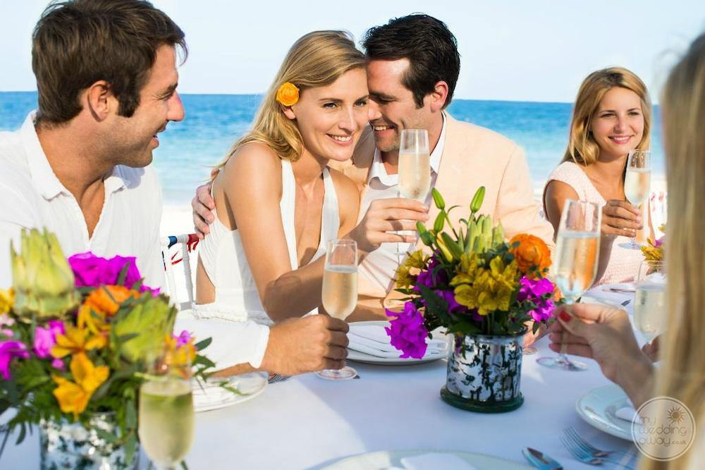 Wedding couple on the beach having a champagne toast with their guests with beautiful flowers