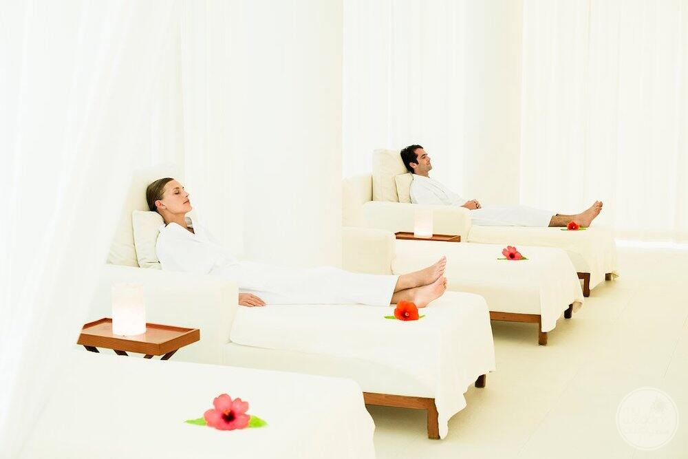 Couple sitting in lounge chairs relaxing in the spa