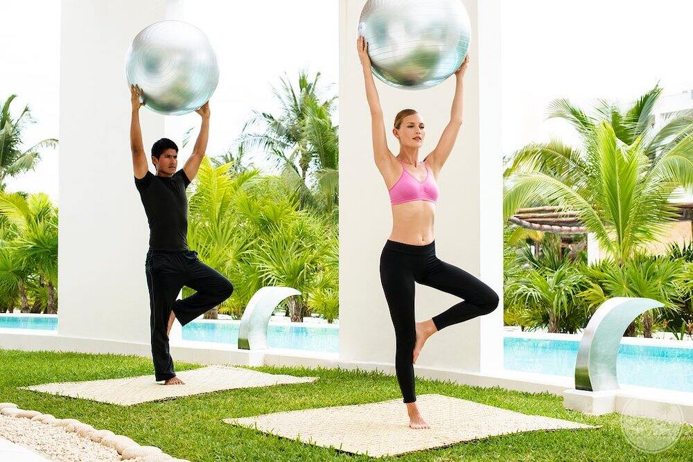 Couple using the exercise balls out or on the grassy area beside