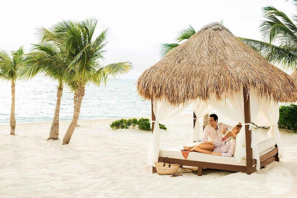 Couple sitting in the beach cabana on the white sand with surrounding palm trees and blue ocean