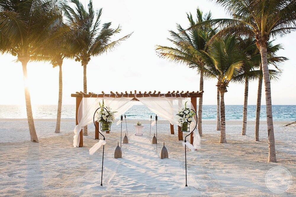 Beach wedding ceremony set up with a white sand green palm trees and flowers