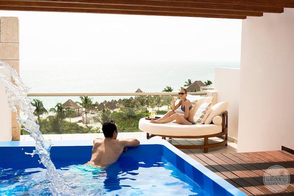 Couple relaxing and enjoying the plunge pool with views of the beach and ocean