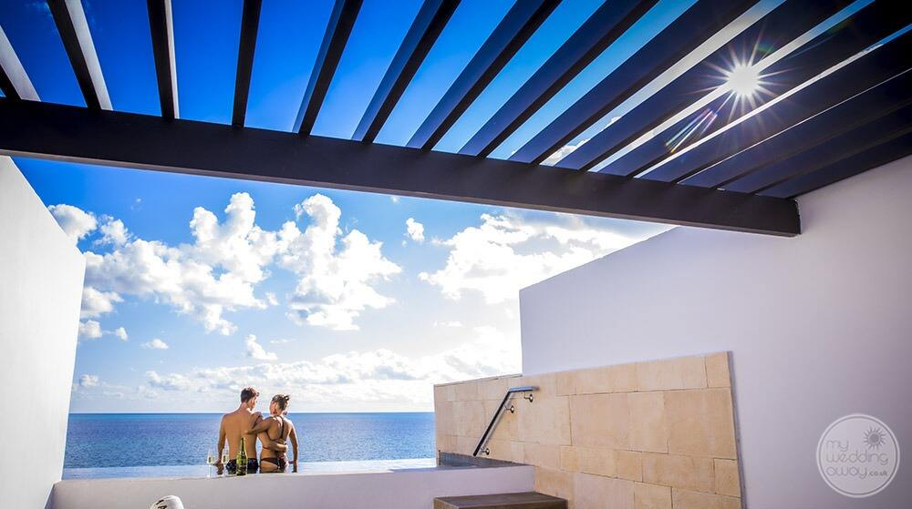 Couple standing together underneath the Sun and blue skies overlooking the ocean from there outdoor Jacuzzi deck