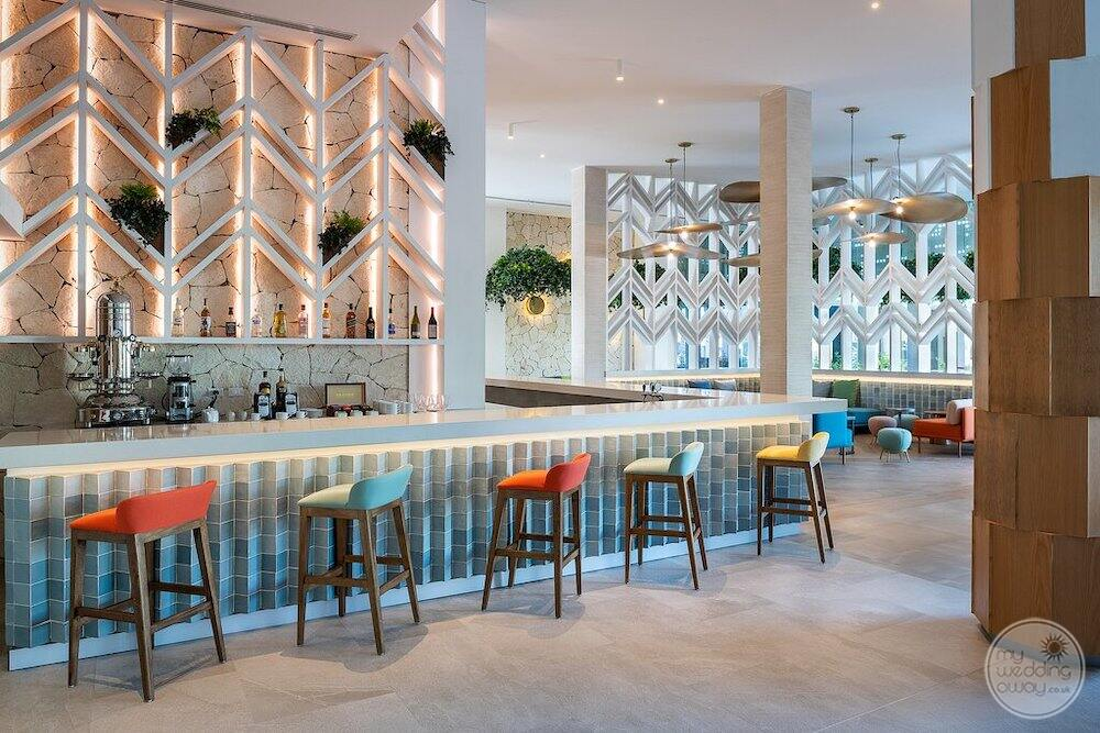 Lobby bar with brightly coloured chairs and expansive room