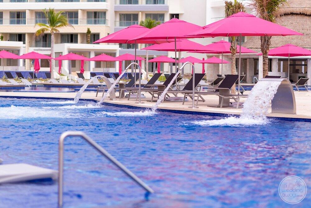 Main swimming pool with spa water features and pink umbrellas and lounge chairs