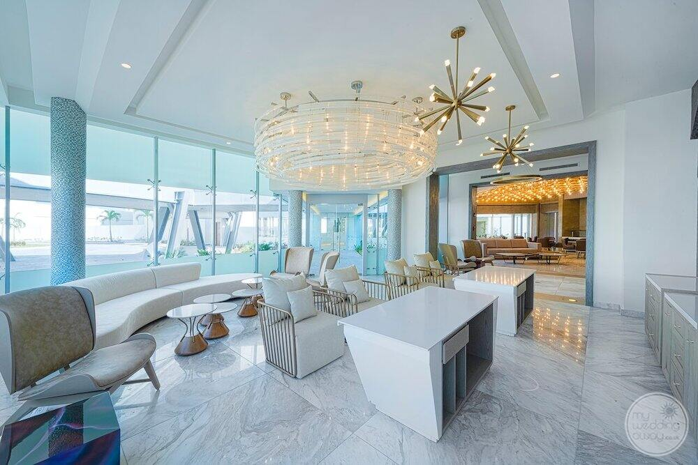 Lounge area with a white couches tables and white chandelier