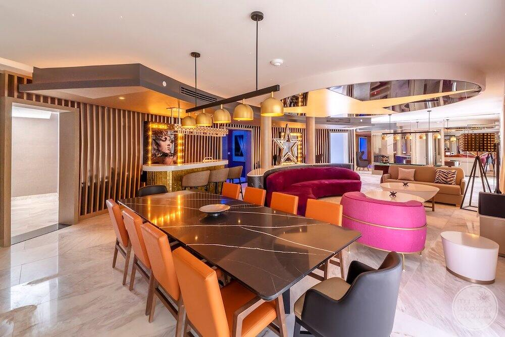 Colourful bar area with orange chairs pink couches blue wall features and yellow lights