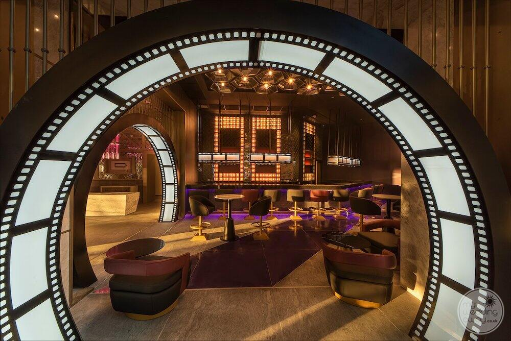 Movie screen style nightclub with purple carpet White reel features