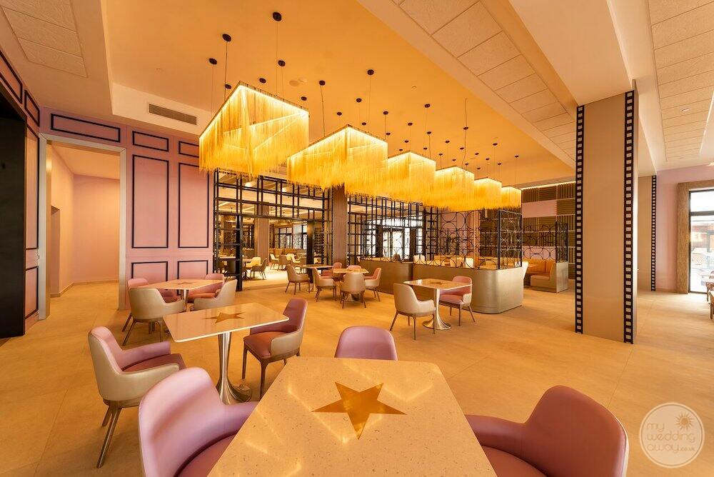 Dining room with yellow string chandeliers pink chairs and tables with stars on them