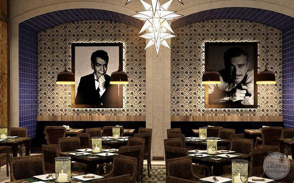 Restaurant with velvet brown chairs banquet style seating and Hollywood memorabilia on the walls