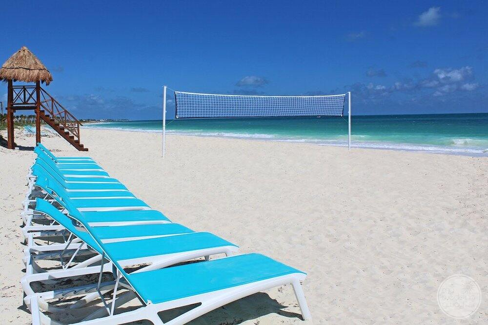 Outdoor lounge chairs on the beach with beach volleyball set up beside the ocean