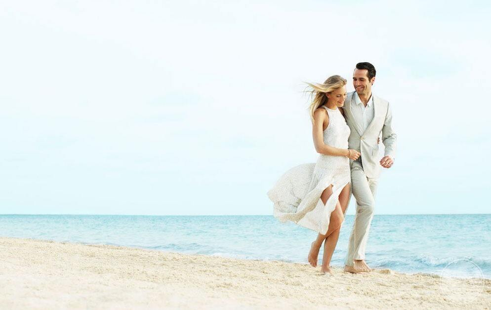 Bride and groom walking along the sand in front of the hotel beside the creepy an ocean