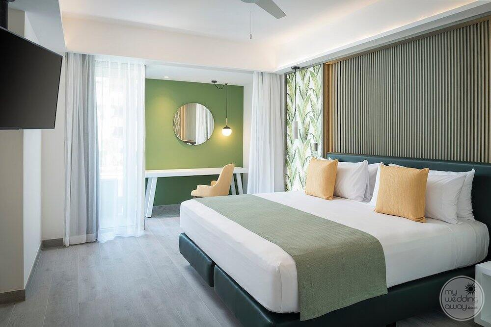 Superior suite with light green and white decor hardwood floor and television