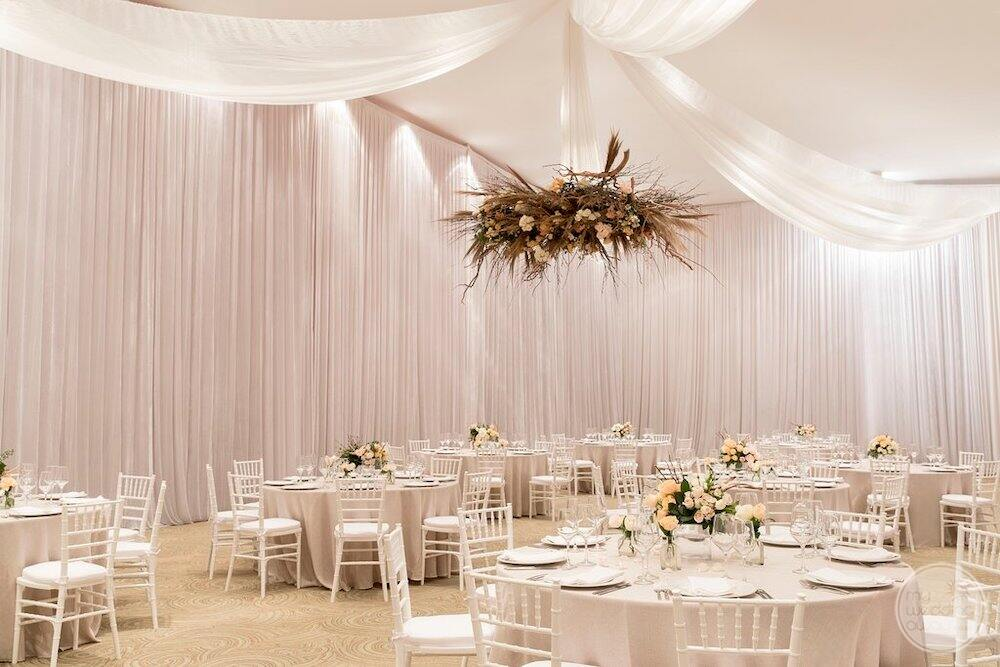 Indoor pool room wedding reception set up with white walls and flower decor