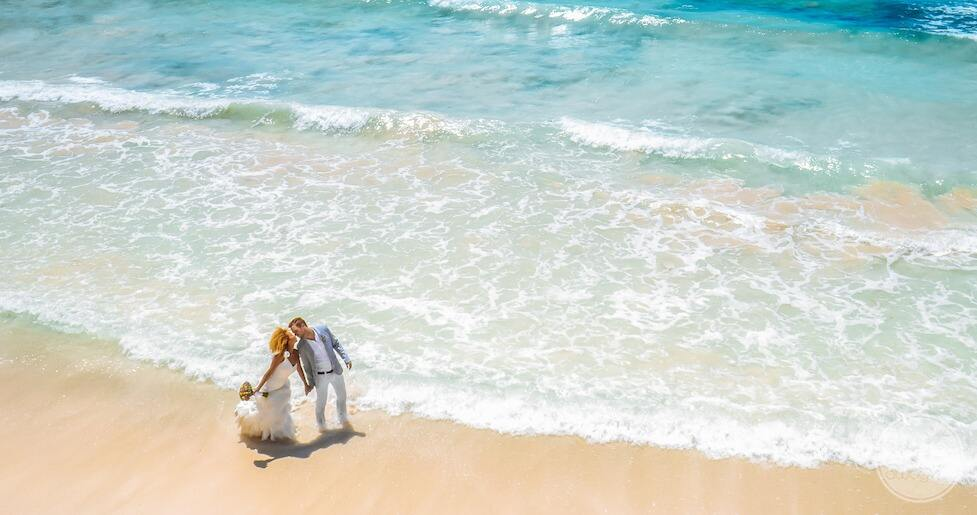 Engaged couple on the beach with wedding rings